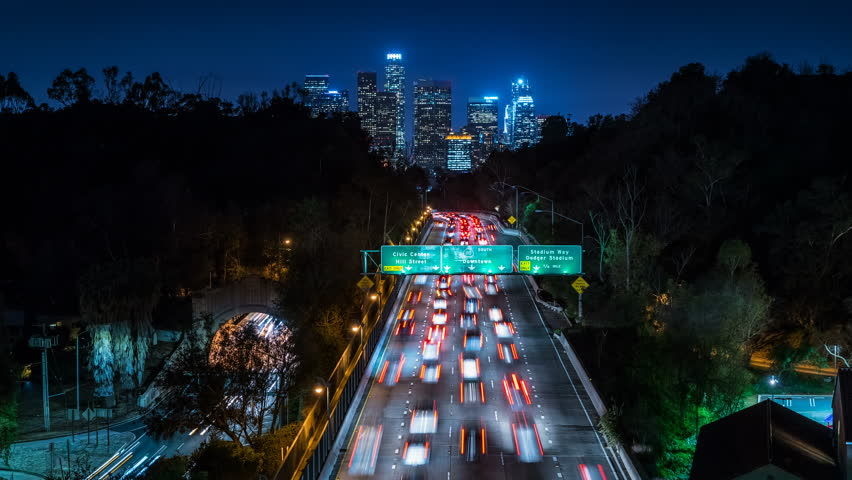 Beautiful view of Los Angeles Skyline from 110 Freeway at dusk. Close up. Traffic passing by. Timelapse. California, United States.   Shutterstock HD Video #19272145