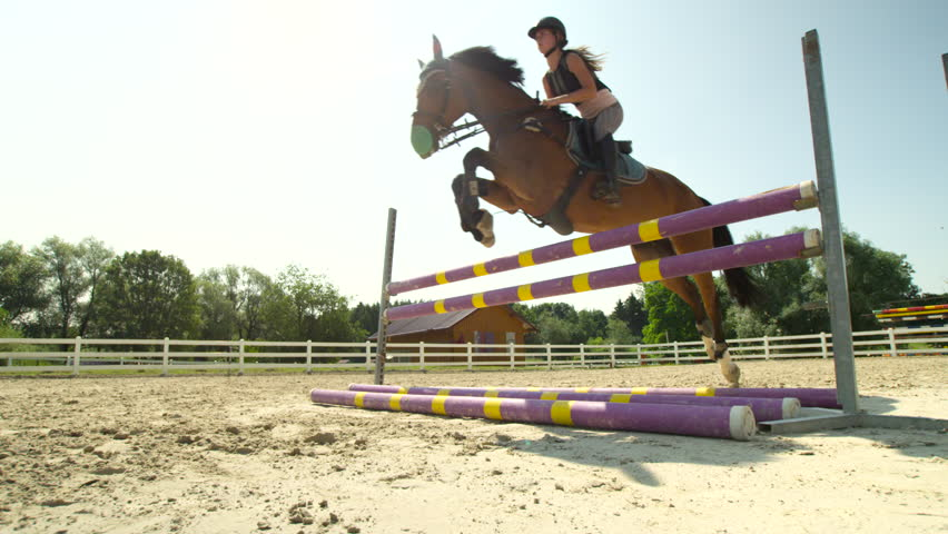 SLOW MOTION, CLOSE UP, LOW ANGLE: Horsegirl riding strong brown horse jumping the fence in sunny outdoors sandy parkour riding arena. Competitive rider training jumping over obstacles in manege