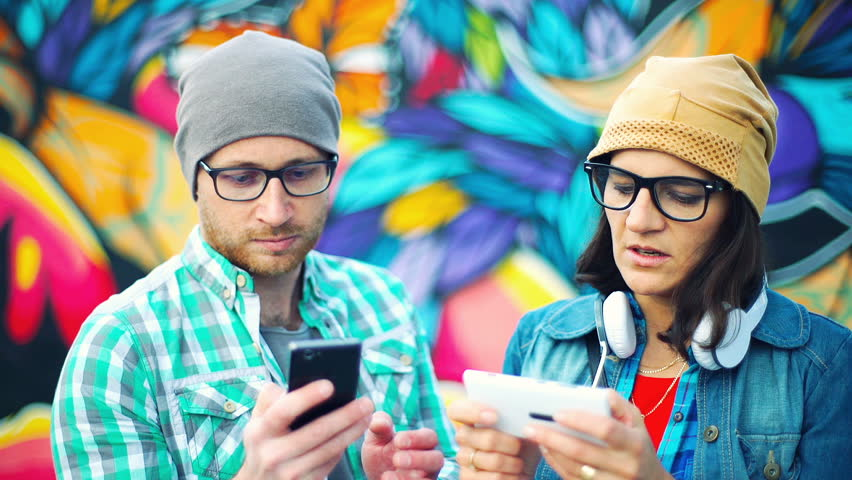 Pair pf hipsters standing next to each other and using smartphones