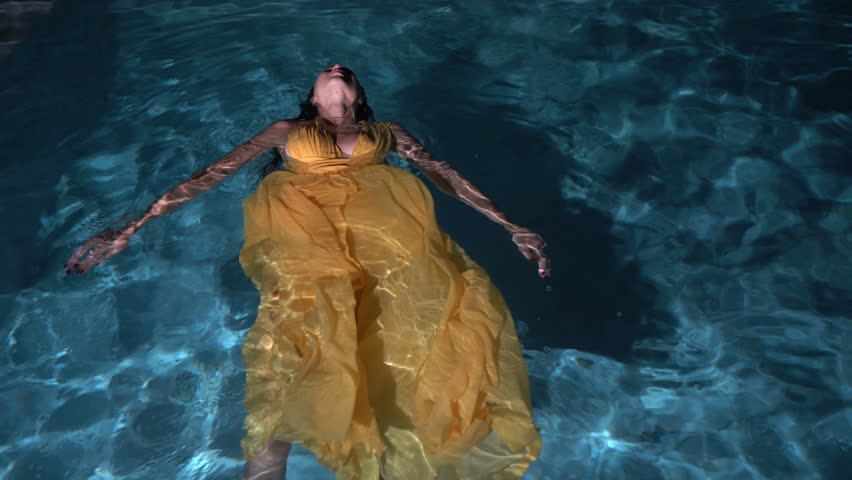 9740ea9c2a6b4 Top view of gorgeous fashion woman with dark hair in elegant yellow dress  lying in water of outdoor pool at night