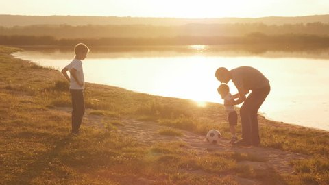 Young family frolicked together to play football football on the beach at sunset with two boys working with his father