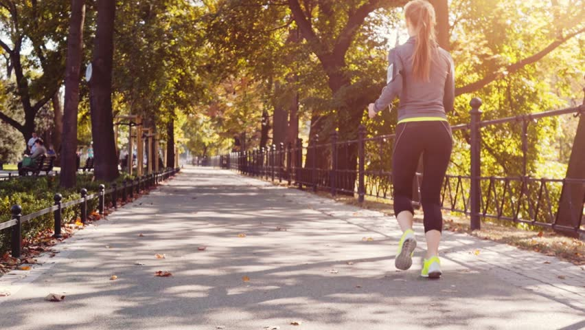 Runner Woman Running in the Sunny City Park Exercising Outdoors. Steadicam STABILIZED shot, SLOW MOTION 120 fps. Sportswoman Listening to Music during Morning Training. Healthy Lifestyle. Lens Flare. #19353265