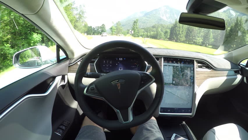 AUTONOMOUS TESLA CAR, JULY 2017:  Unrecognizable person self driving autonomous electric car, navigating and steering without driver on winding countryside road. Vehicles coming on the opposite lane