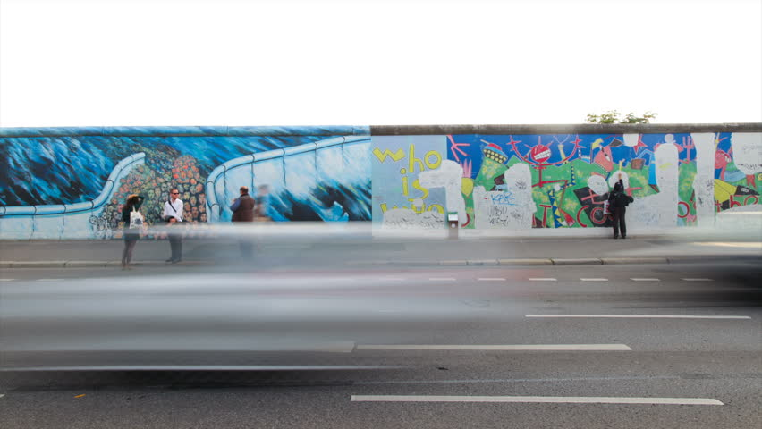 BERLIN, GERMANY, CIRCA 2011: (Time lapse view) Cars drive and people walk by the East side gallery of the Berlin Wall circa 2011 in Berlin, Germany.