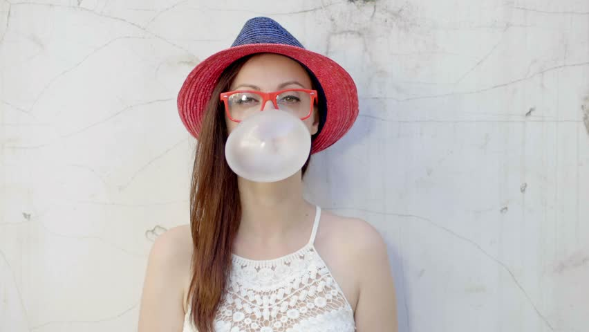 Hipster girl blows big bubble from bubble gum