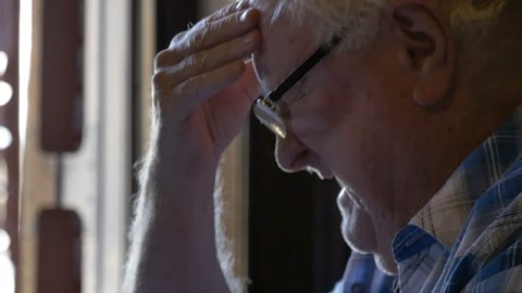 Troubled stressed senior citizen old man scratching head looking overwhelmed