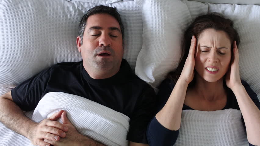Woman (age 30-40) suffers from her partner (age 35 - 45) snoring in bed. Couple lifestyle and people health care concept. Real people. Copy space