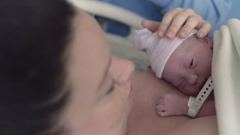 Newborn Baby Girl Laying on Mothers Chest After Delivery in Hospital