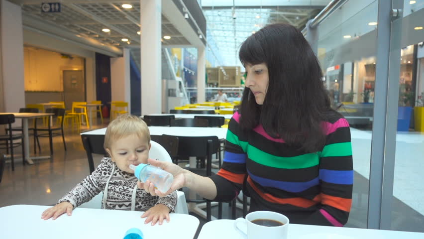 The young woman mother with a young baby son having breakfast in the cafe. | Shutterstock HD Video #19469365