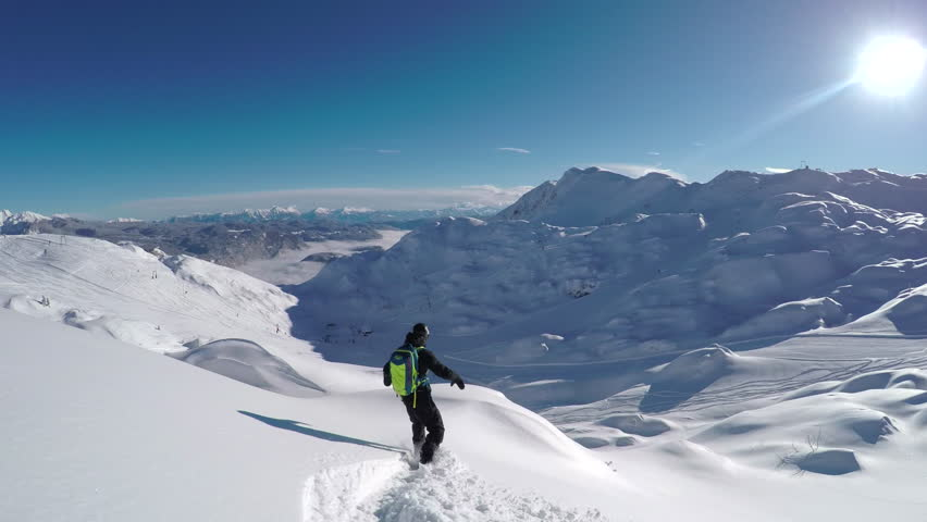 FOLLOW CLOSE UP: Happy snowboarder having fun snowboarding backcountry on a sunny winter day in snowy mountains. Extreme freeride snowboarder riding fresh powder snow off piste in mountain ski resort | Shutterstock HD Video #19480060