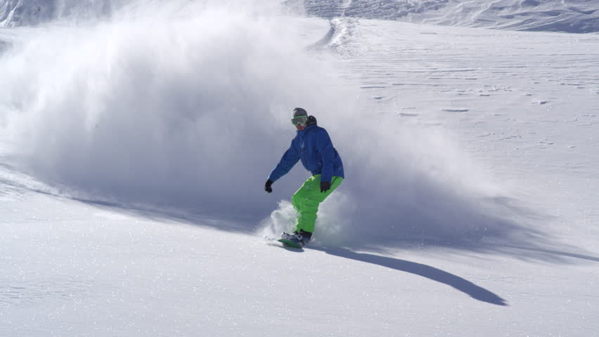 SLOW MOTION CLOSE UP: Extreme snowboarder riding powder and doing powder turns, spraying snow in sunny mountain backcountry. Snowboarder having fun snowboarding in fresh snow off piste | Shutterstock HD Video #19511485