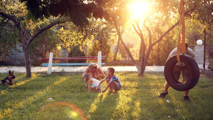 Slowmotion of happy young parents playing with puppy dog and children at home on backyard with sunlight shining over small trees and tire swing