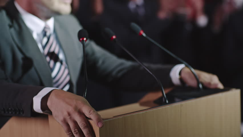 Closeup with selective focus of male politician hands lying on tribune as he delivering passionate speech before public, then making a fist and wildly gesturing | Shutterstock HD Video #19522696