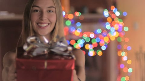 An attractive young woman wearing a Santa hat gives a red wrapped wrapped gift with a silver bow and laughs with colored lights flashing in the background