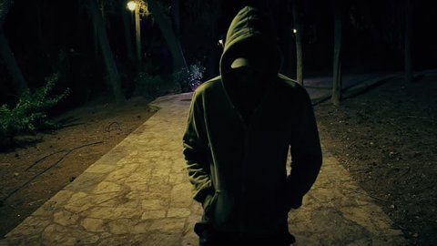 Suspicious hooded figure walks in a dark park at night,100p.A suspicious man wearing a hoodie walks in a dark ominous urban park at night