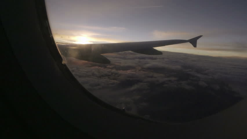 Window seat view of airplane wing in flight at sunset with clouds below | Shutterstock HD Video #19548700