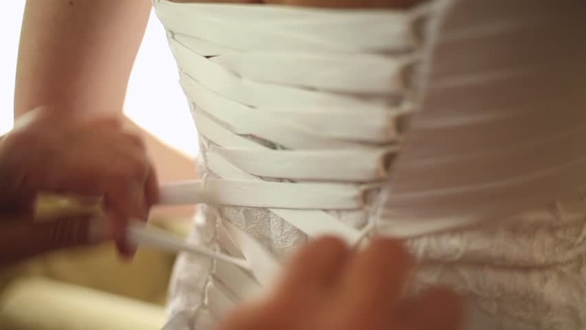 Close up of back of young bride getting ready for wedding ceremony. Mother helping her daughter to dress up bridal dress. Close up of lace and aged female hands. Real time full hd video footage.