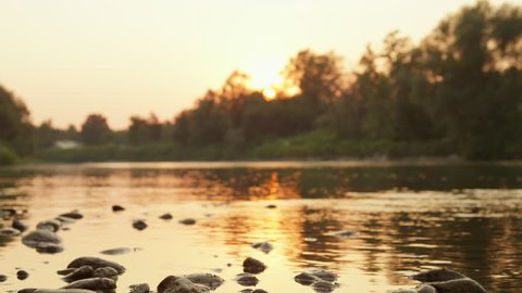 CLOSE UP, DOF: Stunning riverbank shore with big rocks and stones at magical sunrise. Glossy river surface reflecting beautiful fiery sun hiding behind tall lush trees and at magical golden sunset