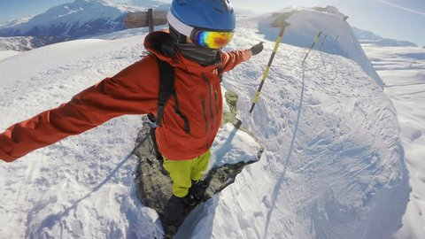 Snowboarder on top of the world, standing on the hill edge, looking down a mountain drop, arms outstretched, camera rotating around his head