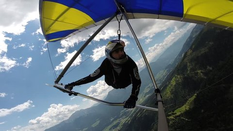Man performs maneuvers on a hang-glider. He rotates in a spiral and handles a thermal, gaining altitude. Shooting with on-board GoPro camera