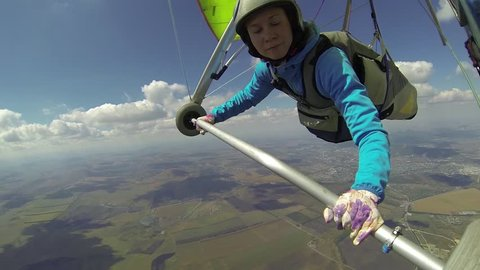 Young woman controls her glider and fly under the cloud base rushing to the finish line on the hang gliding competitions
