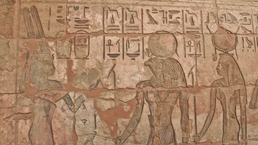 Ancient Egyptian hieroglyphic carvings on a temple wall at Medinat Habu in Luxor Egypt