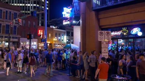 NASHVILLE TENNESSEE / UNITED STATES - JULY 23, 2016: Slow tracking camera shot rounding corner on busy street as people wait outside nightclubs in order to get enjoy party atmosphere & country music.