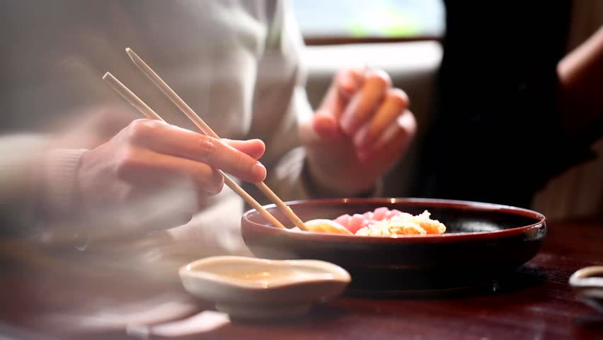 Close up of man hands holding sushi with chopsticks. Closeup of person holding sushi with sticks