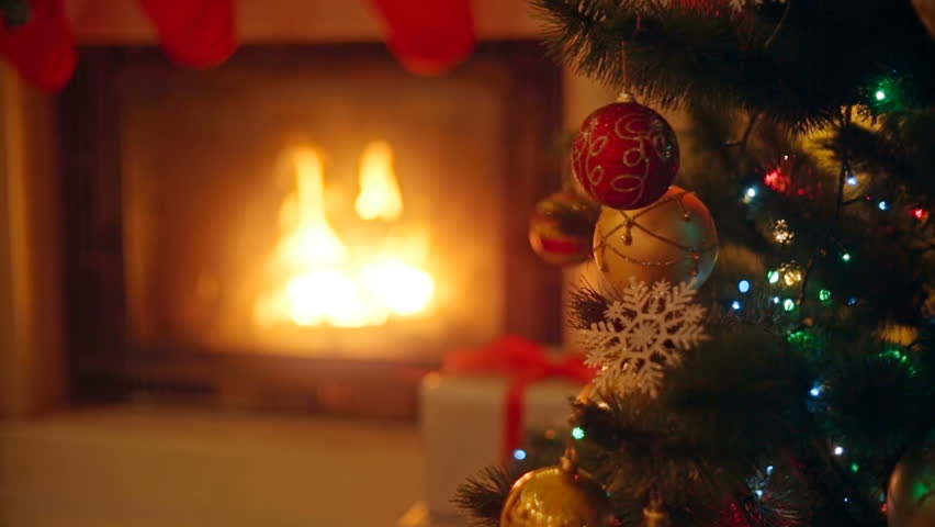 Background with colorful baubles on Christmas tree next to burning fireplace at living room