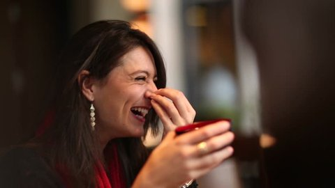 Real laugh and smile. Young woman listening to conversation and spontaneously laughs to funny joke