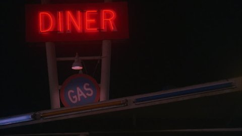 night Rack focus red fluorescent Diner sign pull back Raked right 50's style diner cars people 50's clothing