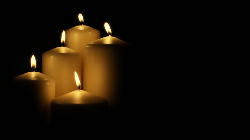 Five flickering candles on the black background.
