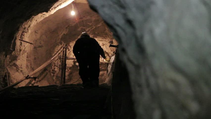 Miner walking inside mine