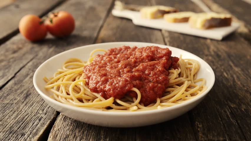 Putting parmesan cheese on spaghetti  with tomato sauce