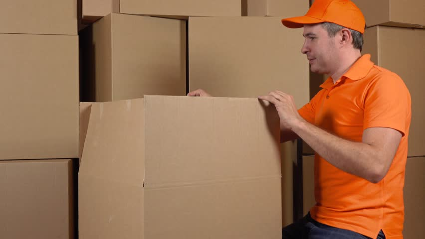 Warehouse worker in orange uniform packaging big carton with duct tape gun. Multiple boxes background. 4K video | Shutterstock HD Video #19735375