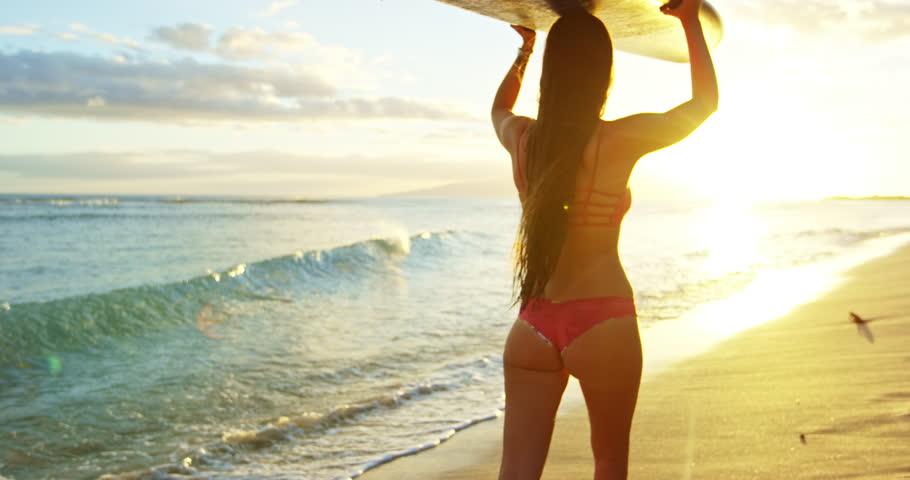 Beautiful surfer girl walking down the beach into the sunset | Shutterstock HD Video #19757227