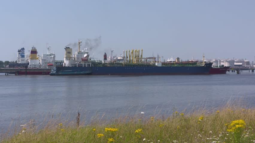 EUROPOORT, SEAPORT ROTTERDAM - JULY 2016: crude oil tanker berthed. plume of black smoke.