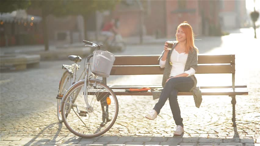 Cute redheaded girl is resting, sitting on a bench in the city. She postponed aside her Tablet and drink coffee