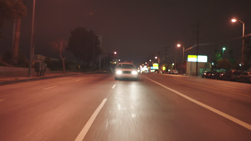 Night MPOV Straight Back Holding front white police car non emergency , city street, small businesses, rundown low income area See suspect criminal backseat Palms , color blue b Has matching shots   Shutterstock HD Video #19823935
