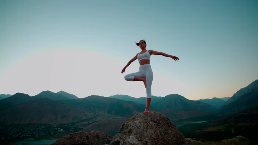 4K beautiful girl in white clothes doing yoga on the beautiful backdrop of the mountains,slow motion