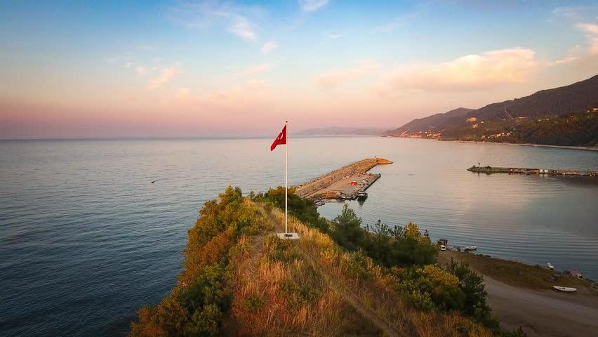 Rotating around the Turkish flag flapping in Catalzeytin a small Black Sea village in Kastamonu, Turkey at sunset.