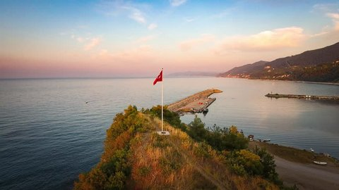 Rotating around the Turkish flag flapping in Catalzeytin a small Black Sea village in Kastamonu, Turkey at sunset.