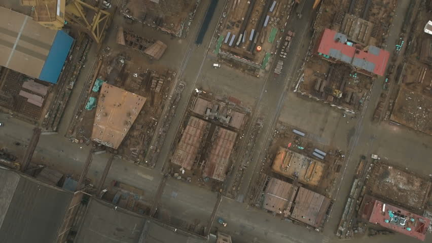 Overhead aerial flight over old and rusty shipyard in China. An example of a sector that helped fuel the country's economic growth, but appears to be struggling these days due to various reasons. | Shutterstock HD Video #19846135