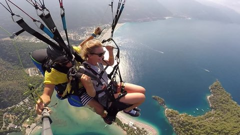 Tandem paragliding. Fear and joy. Extreme touristic Attraction. Paragliders flies over sea coast
