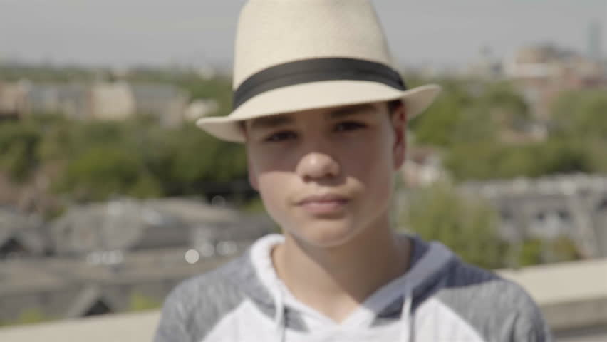 ca5668d988a0 Close up of a good looking teenage boy wearing a very fashionable hat. He  is out on the terrace of a penthouse. 4K UHD.