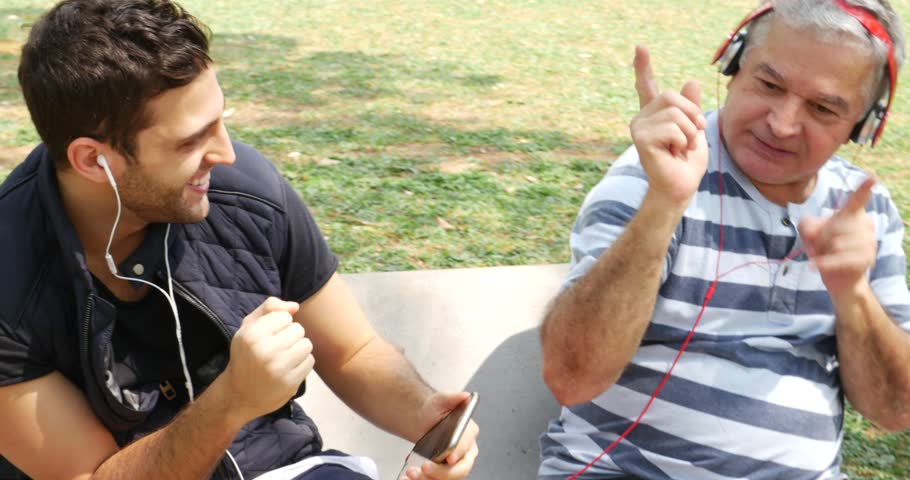 Father and son listening to music and having fun in the park