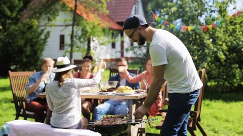 leisure, food , eating, people and holidays concept - happy man grilling meat on barbecue party for his friends and drinking beer from bottle at summer garden