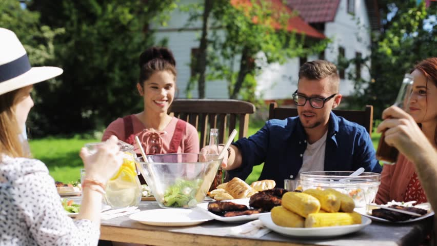 Leisure, holidays, eating, people and food concept - happy friends having dinner at summer garden party | Shutterstock HD Video #19884235