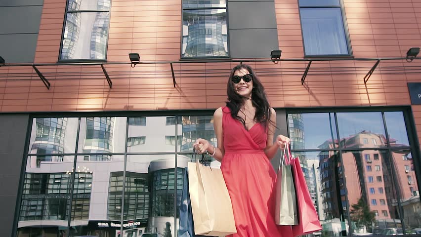 Pretty young girl in red dress holding her shopping bags | Shutterstock HD Video #19885465