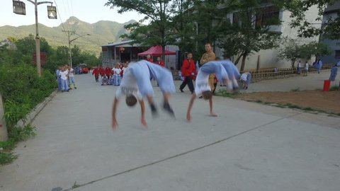 SHAOLIN, CHINA - MAY 2016: Young martial arts students practice back flips in the streets of the Shaolin Wushu area, the 'birthplace' of kung fu, in central China